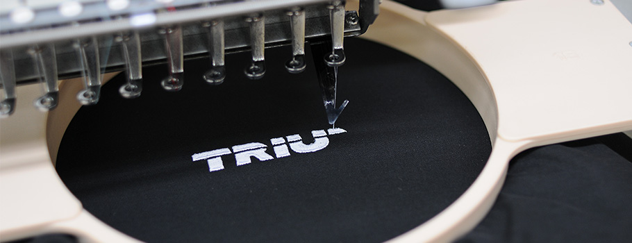 Embroidery machine with Trium logo